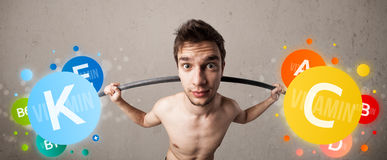 Skinny guy lifting colorful vitamin weights Royalty Free Stock Images
