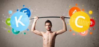 Skinny guy lifting colorful vitamin weights Stock Images