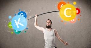 Skinny guy lifting colorful vitamin weights Stock Photos
