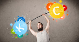 Skinny guy lifting colorful vitamin weights Stock Photo