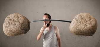Skinny guy lifting large rock stone weights Stock Photo