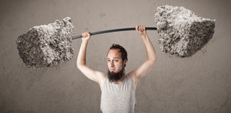 Skinny guy lifting large rock stone weights Stock Images