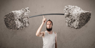 Skinny guy lifting large rock stone weights Royalty Free Stock Photo