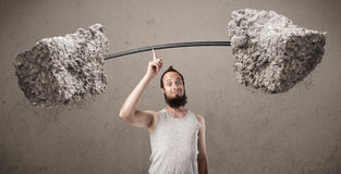 Skinny guy lifting large rock stone weights Royalty Free Stock Photos