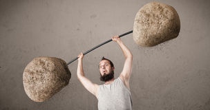 Skinny guy lifting large rock stone weights Royalty Free Stock Photography