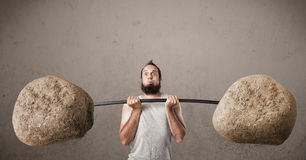 Skinny guy lifting large rock stone weights Stock Photos