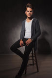Skinny guy posing in studio while sitting with hand in pocket Stock Images