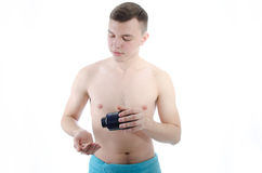 Skinny guy. Taking pills. Young man after a workout. skinny guy. Sports nutrition. Pills. Healthy lifestyle Stock Photos