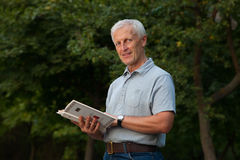 Skinny happy old man. Reading book in the park outdoor Stock Photography