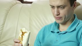 Skinny man eats fast food snack with great enjoyment. guy chewing junk food with big appetite. slow motion. Skinny man eats fast food snack with great enjoyment stock video footage