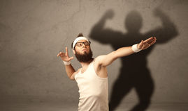 Skinny man with musculous shadow Stock Photography