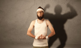 Skinny man with musculous shadow Royalty Free Stock Photography