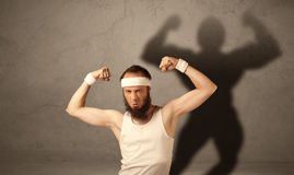 Skinny man with musculous shadow Royalty Free Stock Photo