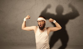 Skinny man with musculous shadow Royalty Free Stock Image