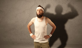Skinny man with musculous shadow Royalty Free Stock Photos