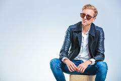 Skinny man wearing sun glasses and leather jacket while sitting Stock Photography