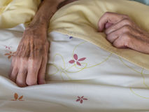 Skinny old hands. The hands of a very old and skinny woman in bed Stock Photography