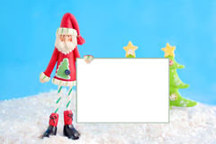 Skinny santa with blank sign. Slim santa claus christmas decoration holding a blank white sign for text on fake snow and blue background Royalty Free Stock Photos