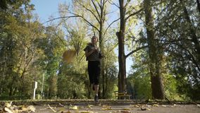 Skinny teenager girl jogging in the park while leaves fall from the trees on a sunny autumn day in weekend in slow motion -. Skinny teenager girl jogging in the stock video footage