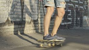 Skinny teenager learning to keep balance on skateboard, youth movement, hobby. Stock footage stock footage