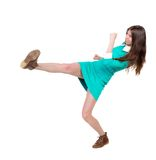 Skinny woman funny fights waving his arms and legs. Isolated over white background. Girl in leather boots strikes. Girl in dress playing football royalty free stock photography