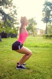 Skinny woman in park, doing squats and running at sunset. Fitness training and workout Royalty Free Stock Images