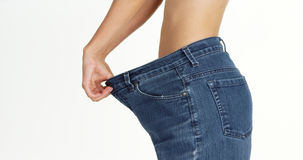 Skinny woman wearing big jeans Stock Image