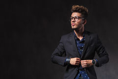 Skinny young man wearing glasses is fixing his jacket in studio Royalty Free Stock Photos