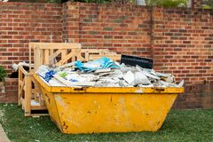 Free Skip Bin Full Of Household Waste Rubbish On The Front Yard. House Clean Up And Renovation Concept Royalty Free Stock Photography - 219858737