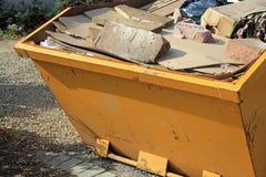 Skip for rubbish. Close-up of yellow skip full of concrete and rubbish Stock Photo
