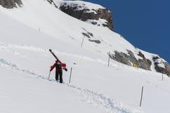 Skipatrouille, die oben einen Berghang trägt große Skis klettert stockfotos