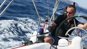 Skipper at the helm controls of a sailing yacht during race