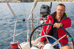 Skipper at the helm controls of a sailing yacht. Sport. Stock Photo