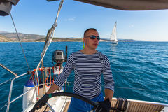 Skipper at the helm controls of a sailing yacht. Sport. Royalty Free Stock Photography