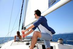 Skipper navigating the sailing boat, woman relaxing. Skipper on sailboat navigating in mediterranean sea Stock Images