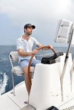 Skipper by the sailing wheel orienting the boat Stock Image