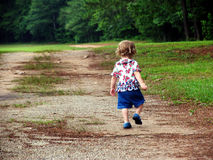 Skipping. Little girl walking up a dirt road royalty free stock photos