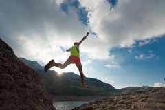 Skipping girl as he runs in the mountains. Girl training run while jumping near an alpine lake in the mountains at sunset Royalty Free Stock Photos
