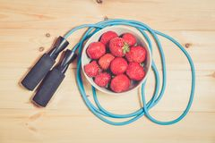 Skipping rope and bowl of fresh strawberry. On wooden background. Top view Royalty Free Stock Photography