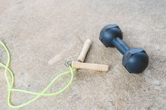 Skipping rope and dumbell for an exercise on cement floor Royalty Free Stock Images