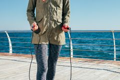 Skipping rope in female hands closeup. Skipping rope in female hands close-up against the sea Royalty Free Stock Image