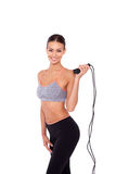 Skipping rope is her way to fitness. Portrait of an attractive young sporty woman holding a skipping rope while standing over white isolated background Stock Images