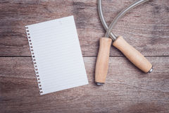 Skipping rope and lined paper on wooden table top view. Close up skipping rope and lined paper on wooden table top view Royalty Free Stock Photos