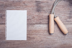 Skipping rope and lined paper on wooden table top view. Close up skipping rope and lined paper on wooden table top view Royalty Free Stock Images