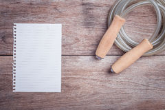 Skipping rope and lined paper on wooden table top view. Close up skipping rope and lined paper on wooden table top view Stock Photos