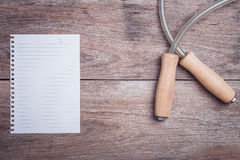 Skipping rope and lined paper on wooden table top view. Close up skipping rope and lined paper on wooden table top view Royalty Free Stock Photo