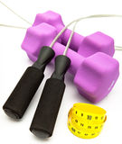 Skipping rope, measuring tape and and Pink dumbbells in a neoprene cover.Still-life on a white background Royalty Free Stock Photos