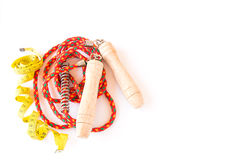 Skipping rope and yellow tape measure on a white background Stock Photo