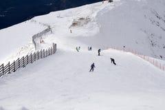 Skiërs en snowboarders die onderaan de helling gaan Stock Foto's