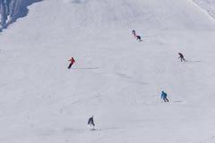 Skiërs en snowboarders die onderaan de helling gaan Royalty-vrije Stock Foto's